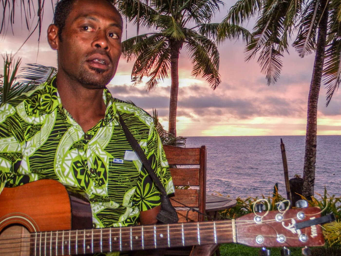 Soni plays guitar as the sun sets at Paradise Taveuni. © Roger Harris
